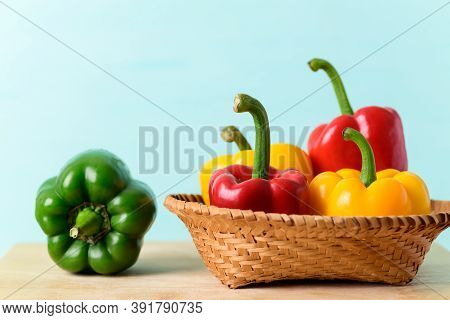 Fresh Red, And Yellow Bell Peppers In A Bamboo Basket And Green Bell Peppers On Wooden Board With Co