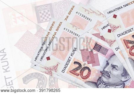 20 Croatian Kuna Bills Lies In Stack On Background Of Big Semi-transparent Banknote. Abstract Presen