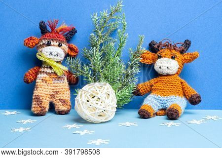 Two Knitted Bull Toys With Christmas Tree, Ball And Snowflakes On Blue Background