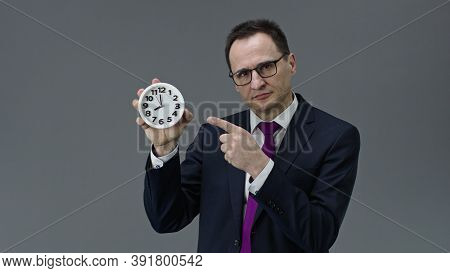Handsome Middle Aged Businessman In Formal Clothes, Tie And Glasses Pointing At Clock In His Hand Wi