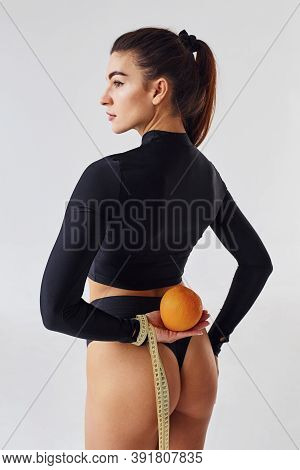 Young Girl With Orange And Measuring Tape In The Studio Against White Background.