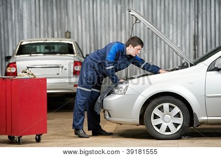 motor mechanic diagnosing automobile car engine before maintenance at repair service station