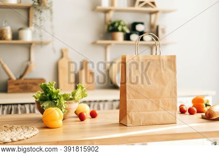Eco Shopping Paper Bag With Fresh Vegetables And Baguette On The Table In Modern Kitchen. Food Deliv
