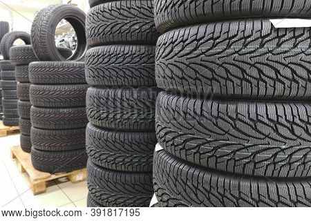 Car Tires In Auto Store. Tires For Sale In A Tire Store - Stacks Of New Tires.