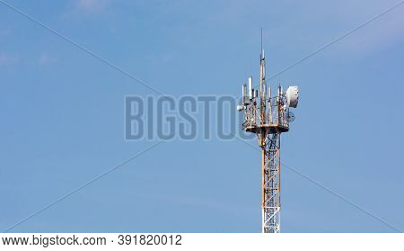 Aerial Of Mobile Communication On A Background Of A Blue Cloudy Sky. High Antenna. Sun Rays And Glar