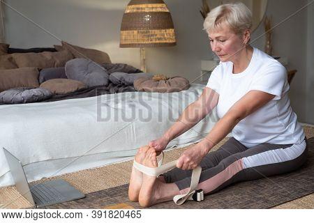 Senior Caucasian Woman Practicing Yoga, Sitting In Seated Forward Bend Exercise, Paschimottanasana P