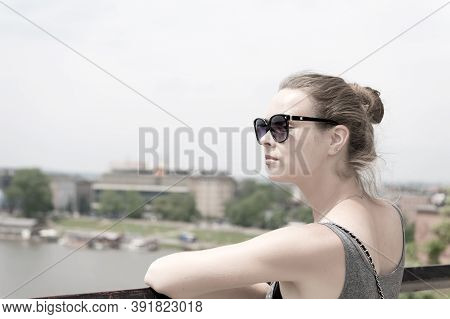 Woman In Sunglasses At Vistula River In Krakow, Poland On Sunny Day. Summer Vacation Concept. Wander