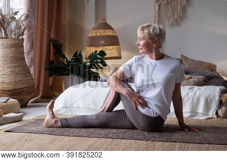 Woman Working Out Doing Yoga Or Pilates Exercise In Half Lord Of The Fishes