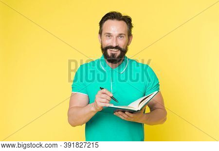 Man Mature Bearded Guy Writing Notes To Notepad. Check What Is Done. Daily Schedule. Developing Habi