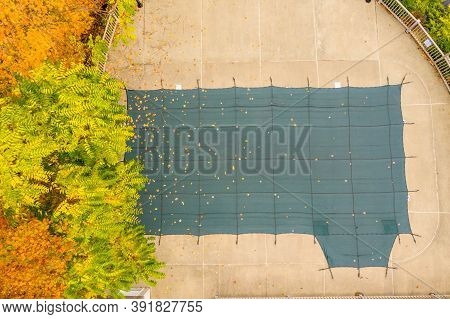Aerial Drone Point Of View Of A Green Plastic Cover On Hoa Swimming Pool Protecting It From Leaves A