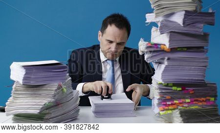 Classic White Collar Sits At Table Littered With Papers, Stamps On Stack Of Unfinished Documents. Ac