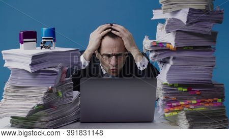 Concentrated Office Worker Businessman Working On Laptop Among Piles Of Paperwork And Stamps On Stac