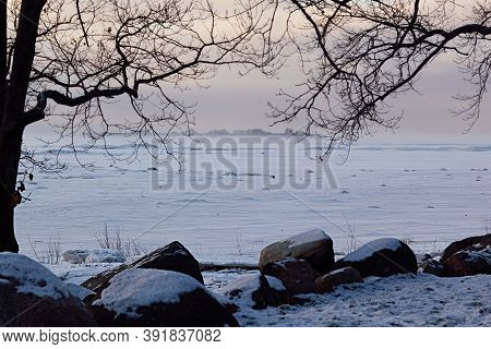 Cold Winter Pastel Colored Landscape With Frozen Shore And Little Island Far Away With Silhouette Bl