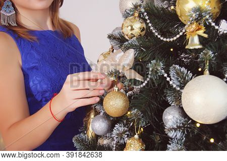 Beautiful Young Girl In A Blue Dress With A Beautiful Manicure Stands Near A Christmas Tree Decorate