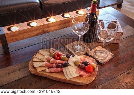 Red Wine With Charcuterie Board On Rustic Wood With Candles Behind A Spread Of Prosciutto Panino, Mo
