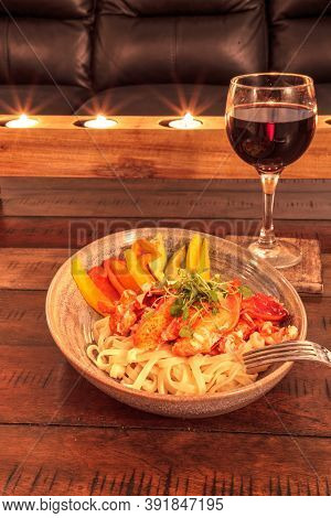 Red Wine With Maine Lobster Over A Bed Of Linguini With Micro Greens, Colorful Peppers And Avocado S