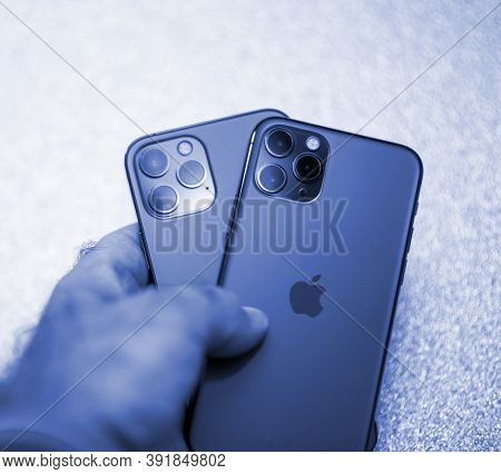 Paris, France - Oct 23, 2020: Pov Male Hand Holding Two Iphones 11 Pro And New 12 Pro Max 5g Smartph