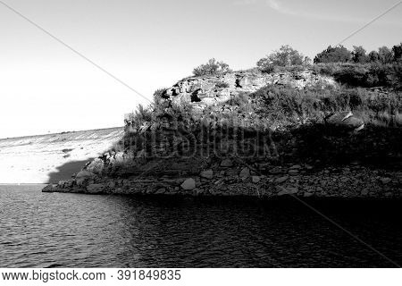 Rough Cliffs And Rocky Shoreline Of Lake Mckinsey Near Amarillo In The Texas Panhandle.