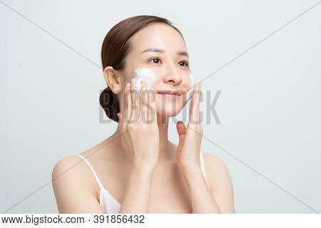 Face Skin Care. Woman Applying Facial Cleanser On Face Closeup. Girl Using Cleansing Cosmetic Produc
