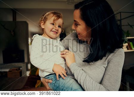 Cheerful Mother And Daughter Playing And Laughing Due To Tickle Standing In Living Room At Home
