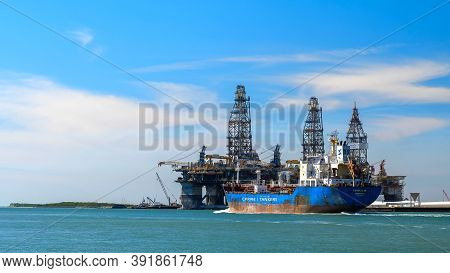 Port Aransas, Tx - 28 Feb 2020: The Caribe Isle, A Crude Oil Tanker Sails Past Oil Rigs In Dry Dock,