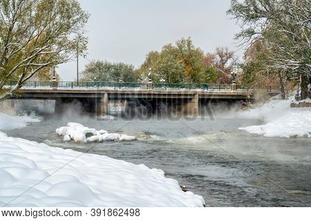 Poudre River is flowing at a whitewater park in downtown of Fort Collins, Colorado, foggy morning fall scenery with fresh snow
