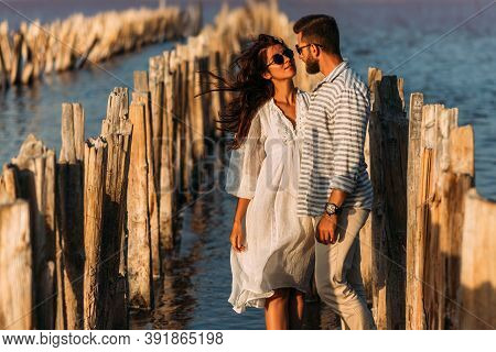 Young Romantic Couple Hugging And About To Kiss In Beautiful Sunset. Portrait Of A Couple In Love At