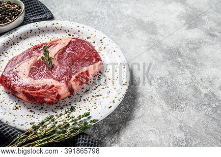 Marbled Beef Fillet Steak. Raw Rib Eye, Ribeye. Gray Background. Top View. Copy Space