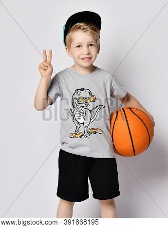 Portrait Of Self-confident Sporty Blond Kid Boy 6-7 Y.o. In Cap, Blue T-shirt With Dinosaur Eating C