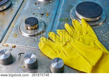 Yellow Gloves On Dirty Stove Top With Food Leftovers. Unclean Steel Kitchen Cooktop Surface With Gre