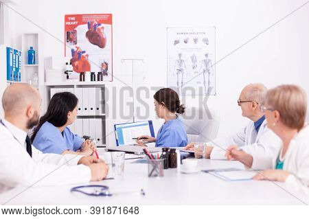 Female Nurse Holding Clipboard Explaining Her Diagnosis In Front Of Medicine Experts During Seminar.