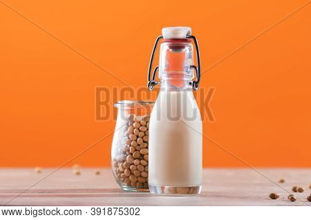 Soy Milk And Soy Bean On Orange Background. Non-dairy Milk Concept. Vegan Drink. Copy Space