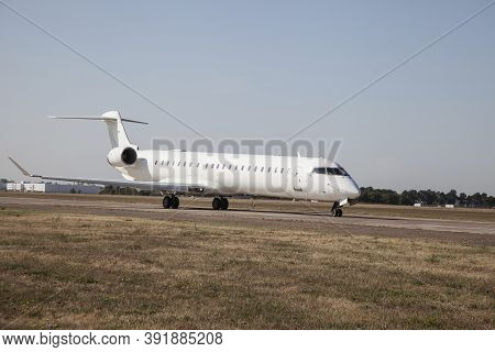 A White Plane On The Airport Runway Is Taxiing. Takeoff And Landing. Arrival And Departure. Place Fo