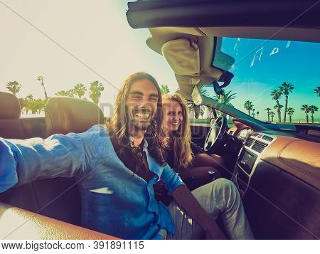 Happy Young Couple Having Fun During Road Trip In Convertible Car. Romantic Lovers Enjoying Time Tog