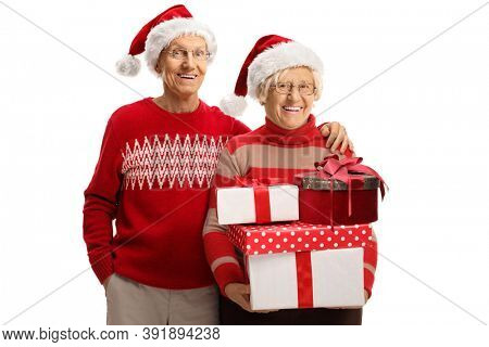 Elderly man and woman wearing jumpers and santa hats and holding a pile of christmas presents isolated on white background