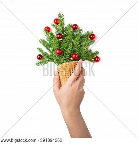 The Girl's Hand Holds An Ice Cream Cone With Sprigs Of Fir And Red Christmas Toys. White Isolated Ba