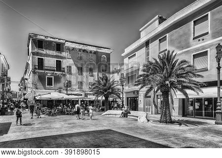 La Maddalena, Italy - August 7: Tourists Enjoying A Sunny Day In Piazza Garibaldi, Central Square Of