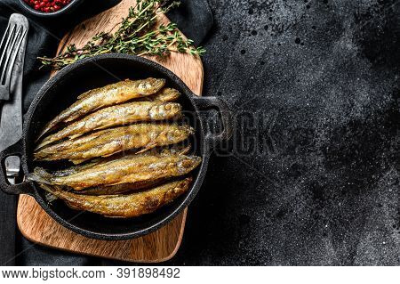 Whole Fried Battered Capelin Fish Served On A Metal Skillet. Black Background. Top View. Copy Space