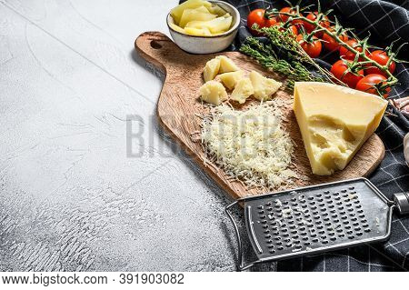 Grated Parmesan Cheese And Metal Grater On Wooden Cutting Board. Gray Background. Top View. Copy Spa