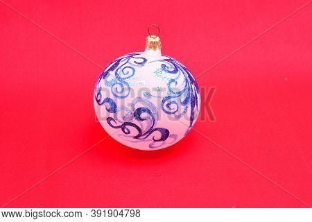 Christmas Toys, Glass Ball, Painted With Colorful Ornaments, On A Red Background