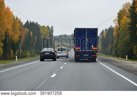 Karelia, Russia - September 30, 2020: Truck And Other Cars Go Along The Highway Through The Autumn F