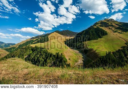Grassy Pass With Mountain Top Views In High Mountains. Young Men And Women Hiking Near Sary Chelek L