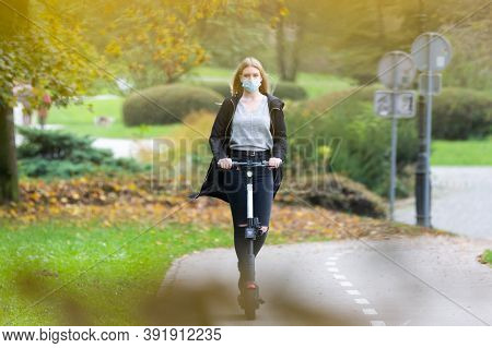 Casual Caucasian Teenager Wearing Protective Face Mask Riding Urban Electric Scooter In City Park Du