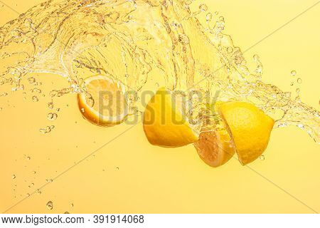Lemon Halves Splashing In Mid Air Against Yellow Background. Splash Photography Background