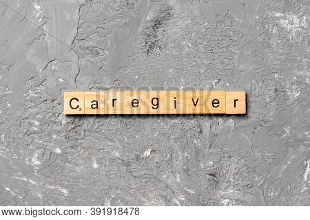 Caregiver Word Written On Wood Block. Caregiver Text On Table, Concept