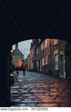 Frome, Uk - October 04, 2020: View Through A Tunnel Of A Man Walking His Dog On A Rainy Day In Frome