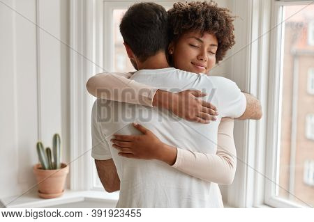 Pleased Dark Skinned Young Woman Gives Warm Hug To Her Boyfriend, Being Pleased, Pose Near Window, H