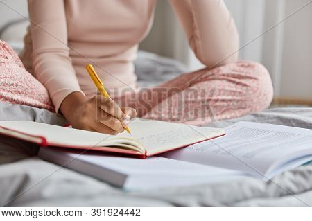 Cropped Image Of Unrecognizable Woman In Nightclothes, Writes Down Information In Notepad, Rewrites