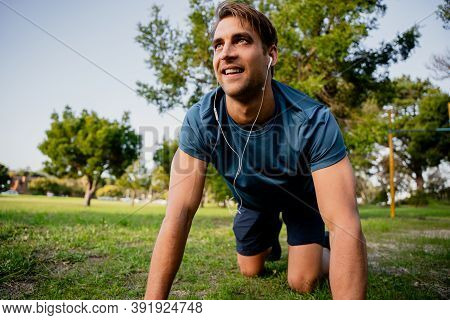 Attractive Young Male Athlete Smiling On Hands And Knees Exercising In Luscious Outdoor Park With Ea