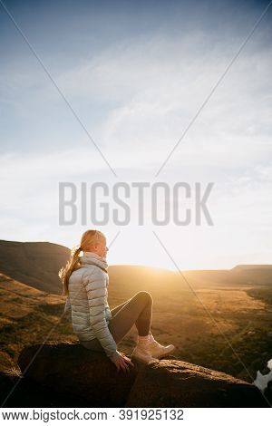 Young Caucasian Teen Sitting On Top Of Boulder Watching Sunset Hiking Luscious Mountain